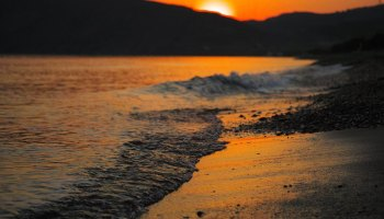 Gentle waves rolling onto a beach with an orange sun setting over dark hills in the background