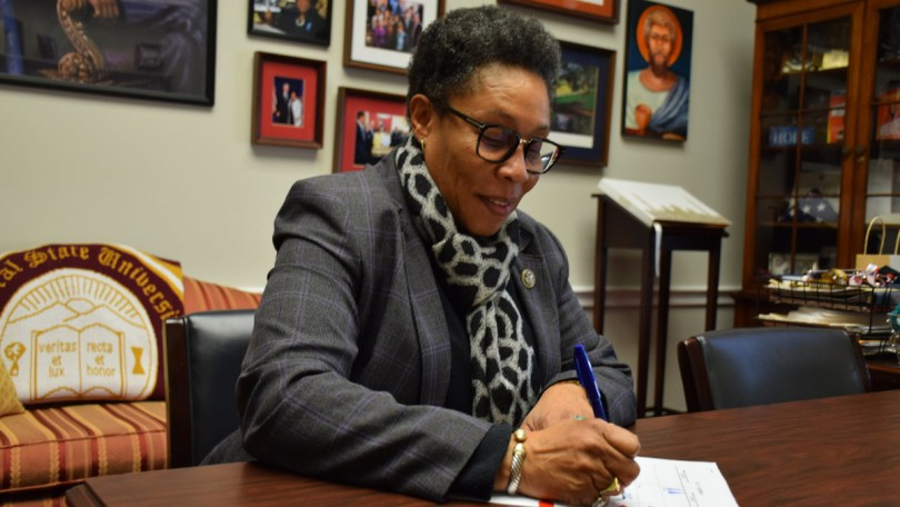 Photo of Housing and Urban Development (HUD) Secretary Marcia Fudge at desk signing paper