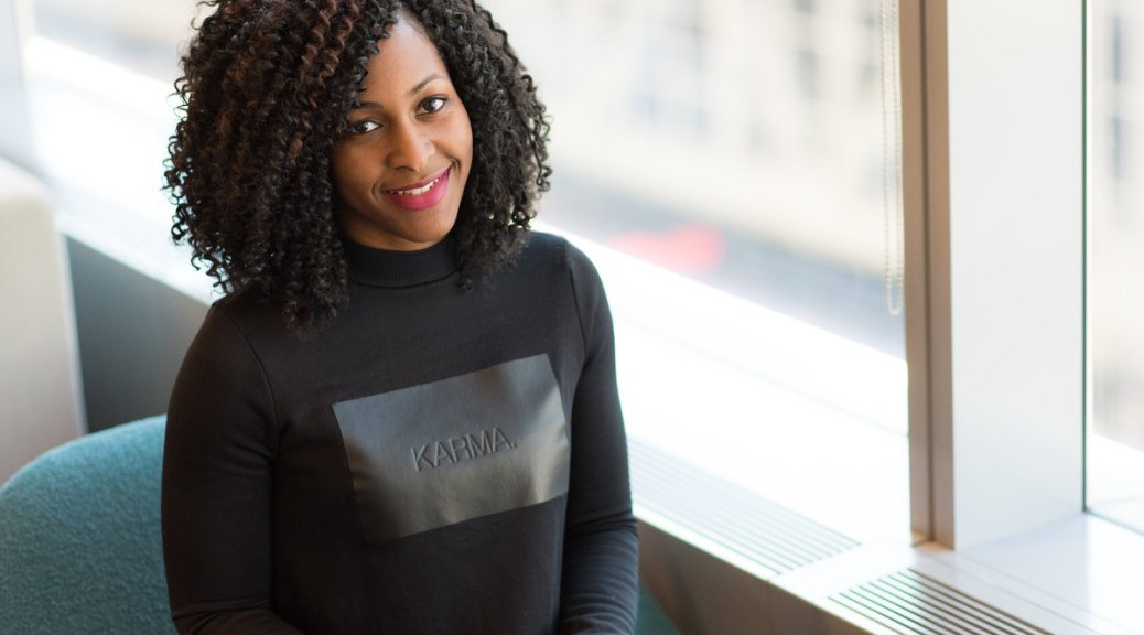 "Black- and female-presenting individual in a black long-sleeved shirt with the words ""Karma"" imprinted on it poses by a window with a laptop computer on her lap."