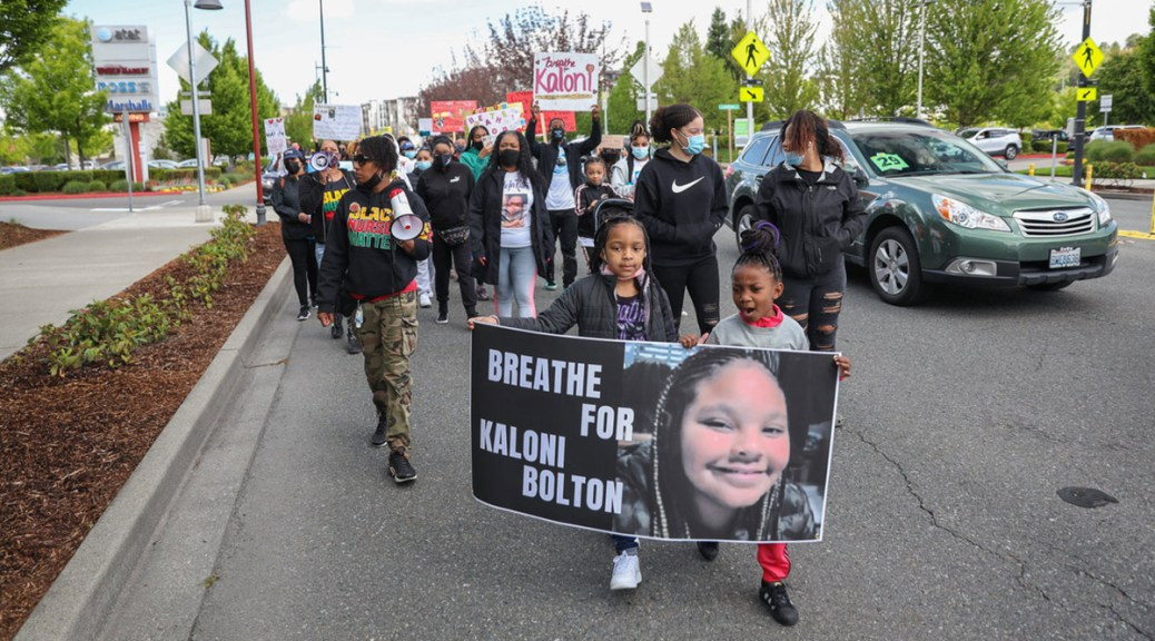 """Renton-area nurses march in solidarity with two Black youth in the front carrying a sign that reads """"Breathe for Kaloni Bolton."""""""