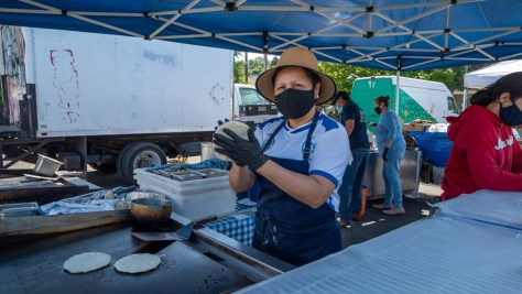 A vendor prepares some fresh pupusas at Lily's Salvadorean Catering booth at the Columbia City Farmers Market.
