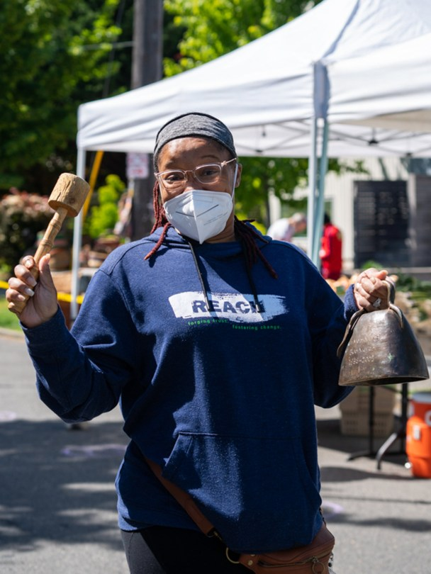A bell ringer walks through the Columbia City Farmers Market