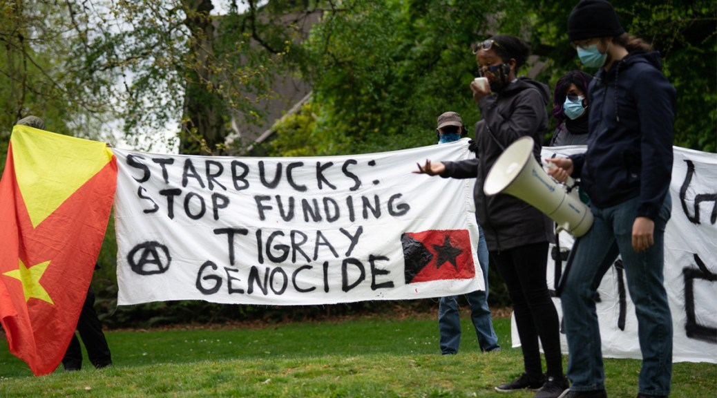 Activists rally at Seattle's Volunteer Park while speakers voice opposition to the ethnic oppression happening in the Tigray region. A handmade sign reading 'Starbucks stop funding Tigray Genocide' is held in the background.