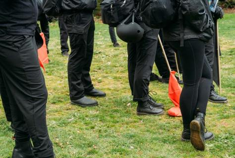 """Protesters dressed in all black, commonly known as """"Black Bloc"""" stand in a group while listening to speakers at the park."""