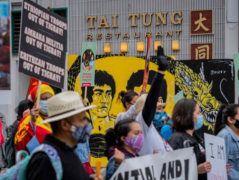 May Day protesters congregate themselves at the intersection of South King Street and Maynard Avenue South in front of the Tai Tung Restaurant with a black and yellow mural of a dragon painted.