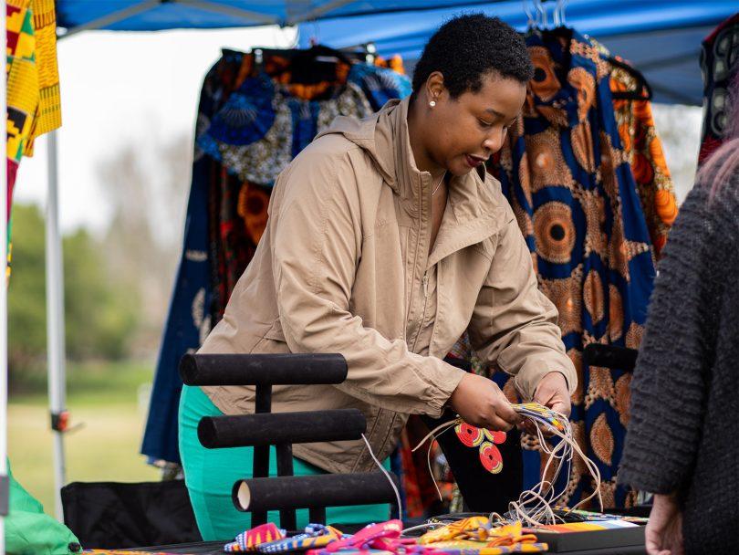 Angela shows a customer handmade jewelry from the Maasai people of Kenya.
