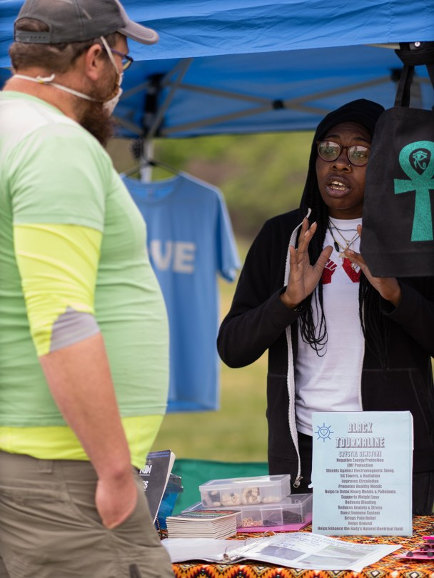 Ma'at CC, owner of ExpressionsByCC LLC, explains her products to a customer.