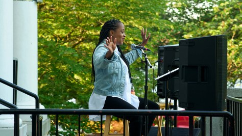 Photo of Dedra D. Woods performing onstage, sitting on a stool and speaking into a mic, her arms and palms outstretched.