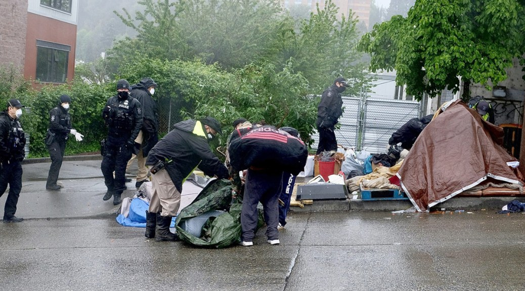 People gather their belongings during a May 20, 2020 sweep of an encampment in the Chinatown-International District.