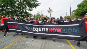 """A march in support of participatory budgeting and increased funding for the Black community, marchers carry a banner with text that reads, """"King County Equity Now.Com"""""""