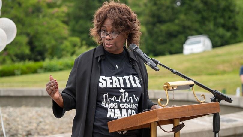 Photo of Seattle King County NAACP President Carolyn Riley-Payne reminding people to take a moment to read the names on the placards lining the entrance to Martin Luther King Jr. Memorial Park.