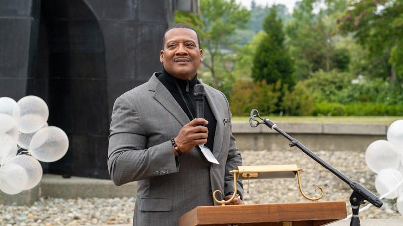 Photo of Reverend Dr. Leslie Braxton delivering a poem at a podium in Martin Luther King Jr. Park.