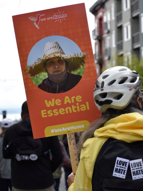 """Protester carries a sign of a farmer that reads """"We are Home; We are Essential."""""""