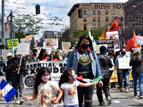 The Trabaiadorxs Esenciales y Excluidxs march passes the Bush Hotel on South Jackson Street.
