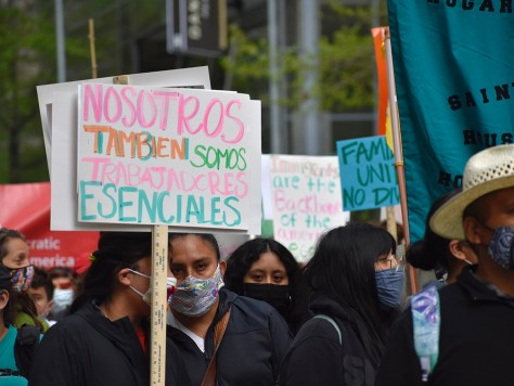 """Protesters carry a sign that reads, """"Nosotros tambien somos trabajadores esenciales,"""" which translates to """"We are also essential workers."""""""