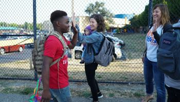 a student receives high-fives from parents outside Rainier Beach High School