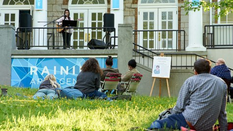 """Rheanna Atendido performing work from Justin Huertas at """"The Campfire Festival"""" while spectators sit on the lawn in front of her."""