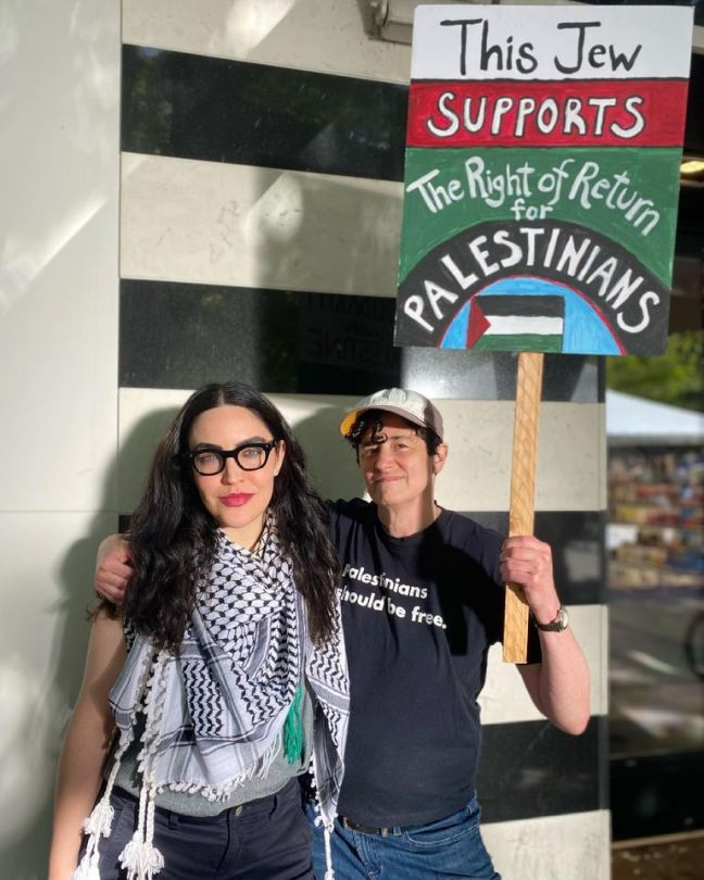 Photo of two women, one holding protest sign