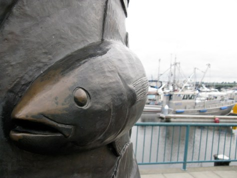 Metal-carved fish sculpture with fishing boats in the background.