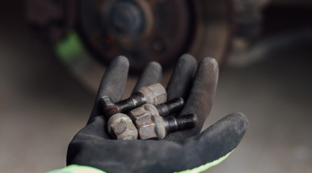 Photo of a mechanic holding lug nuts in his hand and a brake disc in the blurred background.