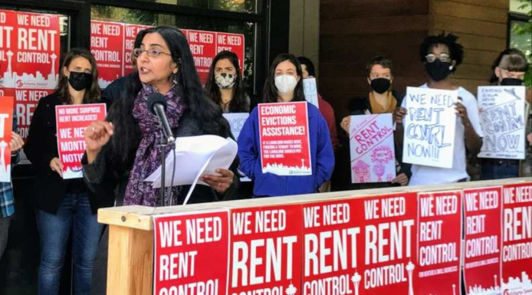 """Seattle City Councilmember Kshama Sawant holding a rally for rent control. Red signs with white text that read """"We Need Rent Control"""" surround her."""