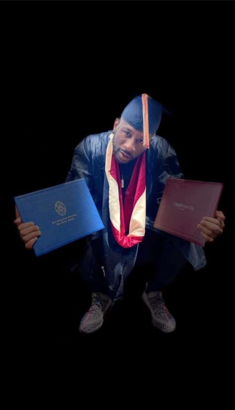 Drew Campbell posing with his academic degrees in his graduation cap and gown.