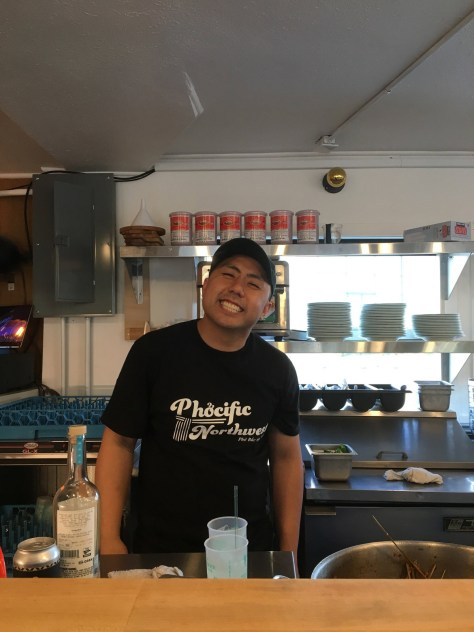 Photo of Khoa Pham standing behind a kitchen counter, smiling boradly.