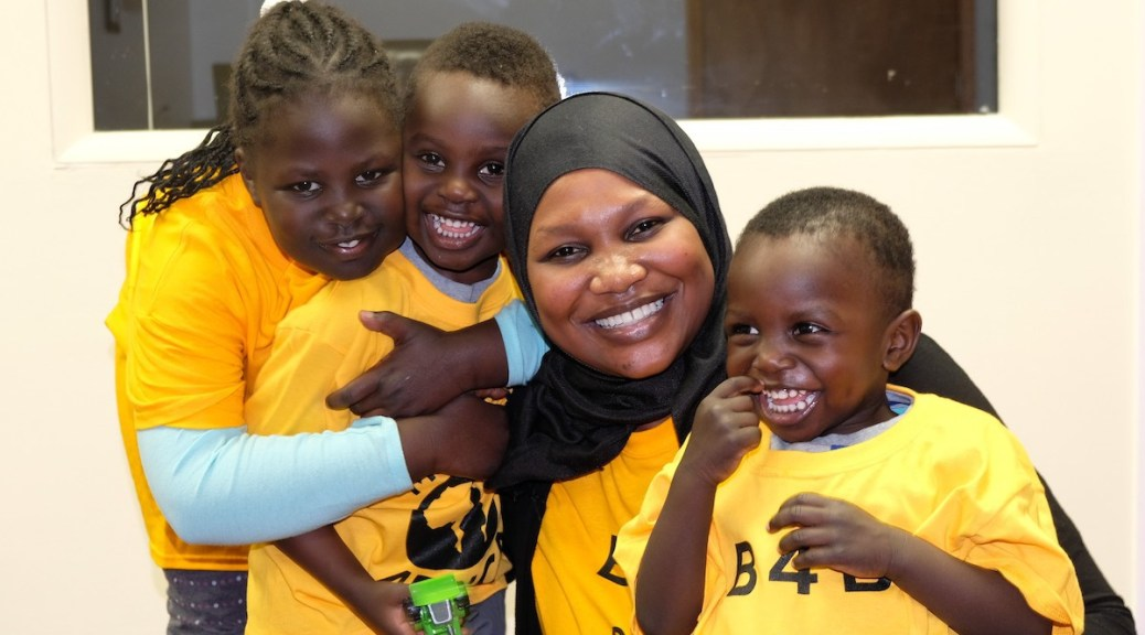 Three Black-presenting youth and a Black-and-female-presenting individual wearing a head covering hug and pose for the camera, all of them wearing bright yellow t-shirts.