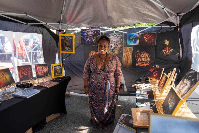"""Photo of Shea Black standing with her art in her tent at """"Honoring Our Black Wall Streets."""""""