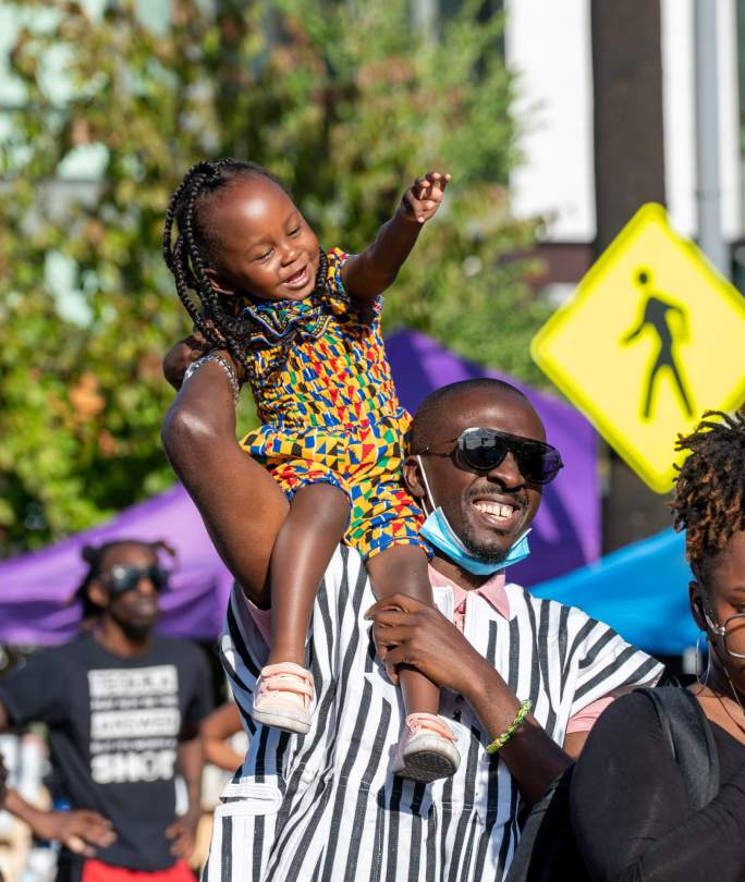 """Nana Ahmed and 2-year-old Jameela enjoy a performance during """"Honoring Our Black Wall Streets."""""""