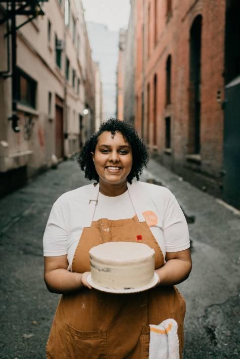 Hana Yohannes smiling and holding a cake outside.
