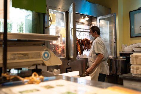 A Kau Kau Restaurant employee prepares to slice some roasted barbeque duck.