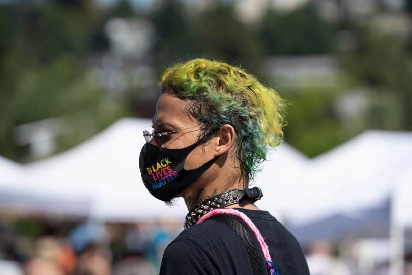 A person wears a rainbow Black Lives Matter mask.