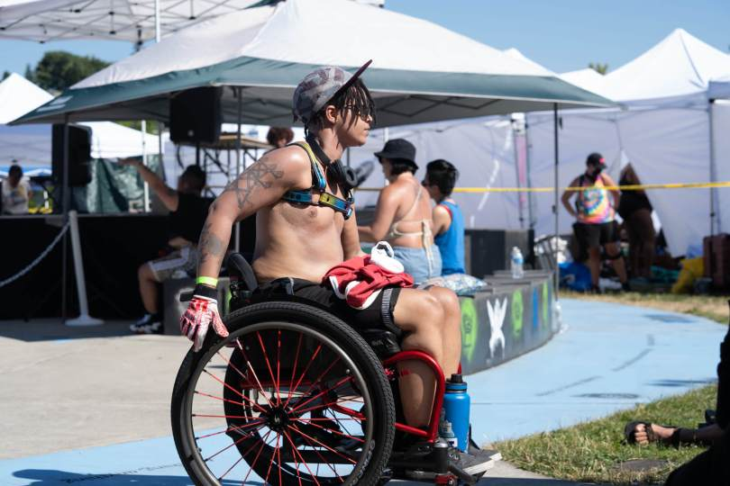A person with dreads using a wheelchair moves across the dancefloor at Taking B(l)ack Pride.