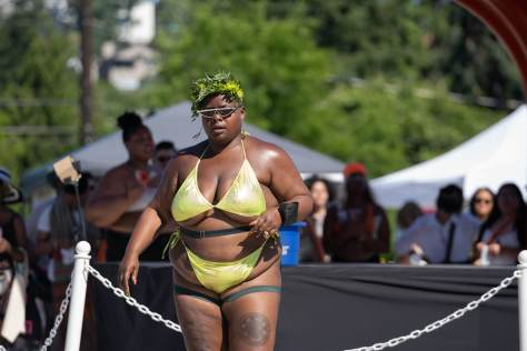 A beautiful Black person in a gold bikini and flower headdress.
