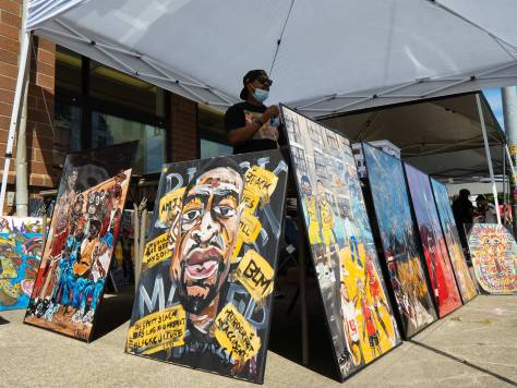 Rodney King (center), owner of King's Pen LLC, showcases his unique art that commentates on topics such as activism, sports, and rap.