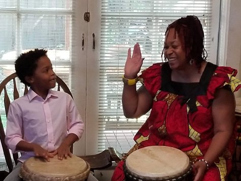 Ellington and Ms. Afua practice playing West African djembe drums