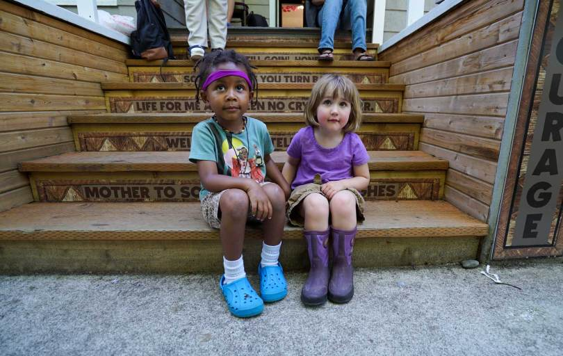 Two youth sit on the outdoor steps of Wa Na Wari during the nonprofit's Juneteenth outdoor celebration.