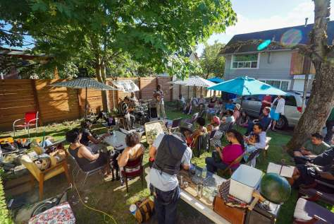 Individuals gathered in the backyard of Wa Na Wari to celebrate Juneteenth with food, drink, and live music from the Blue Meadows Trio.