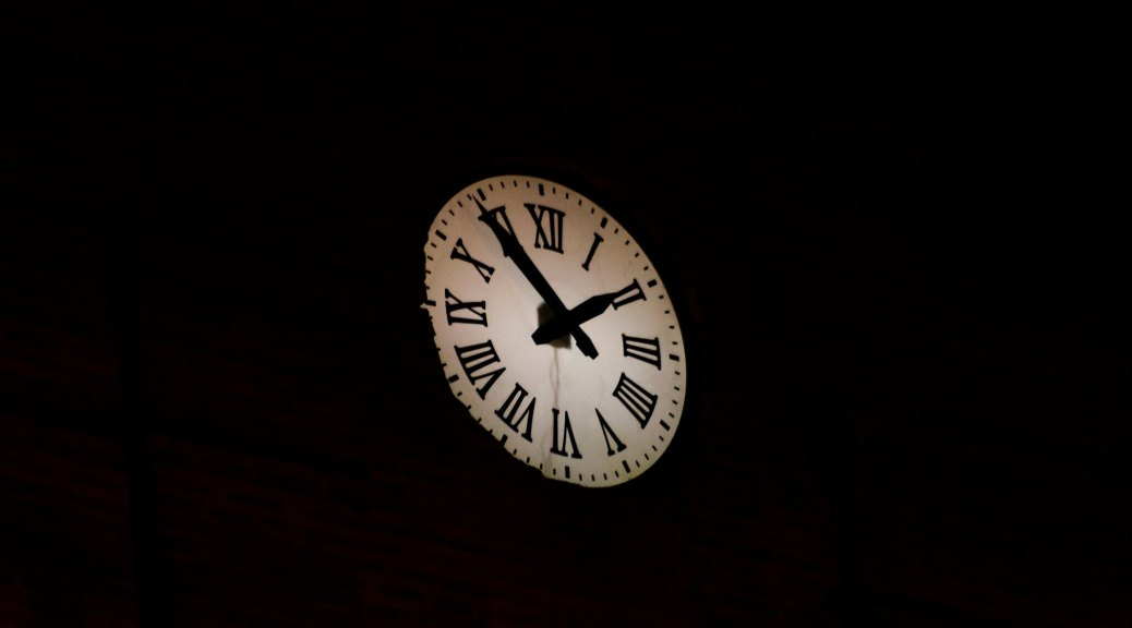 Image of a clock face with roman numerals against black background.