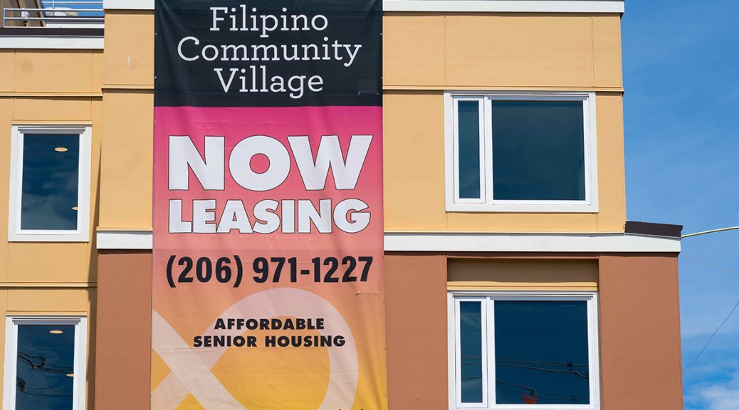 """A """"Filipino Community Village NOW LEASING"""" sign hangs on the side of a newly constructed apartment building."""