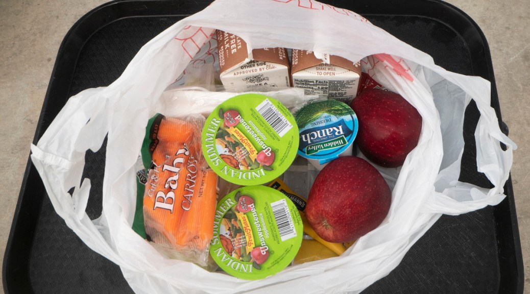 Photo of a sack lunch containing milk, ranch dressing, baby carrots, apples, and juice.