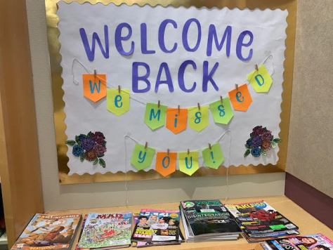 """Photo of a sign reading """"Welcome Back"""" in purple letters with an orange, yellow, and bright-green banner strung beneath the words that reads """"We Missed You!"""""""