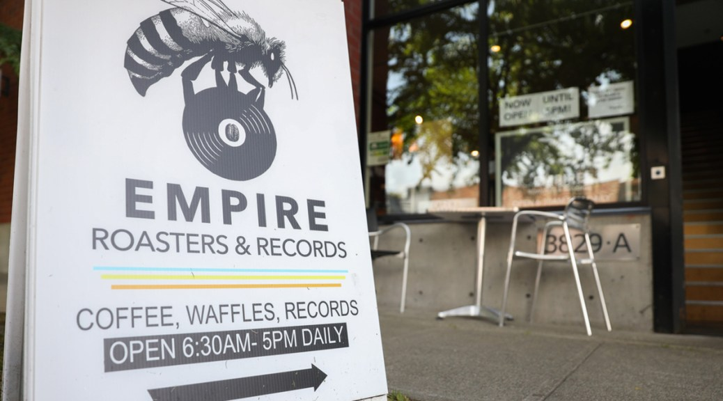 Photo of the exterior sign for Empire Roasters & Records with a bumblebee sitting atop a record.