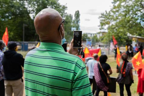 A man livestreams the protest to social media from his phone.