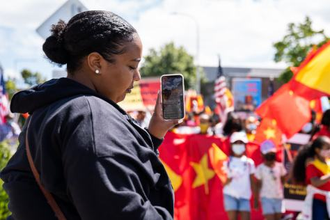 A woman livestreams the march down Easter Yesler Way to social media.
