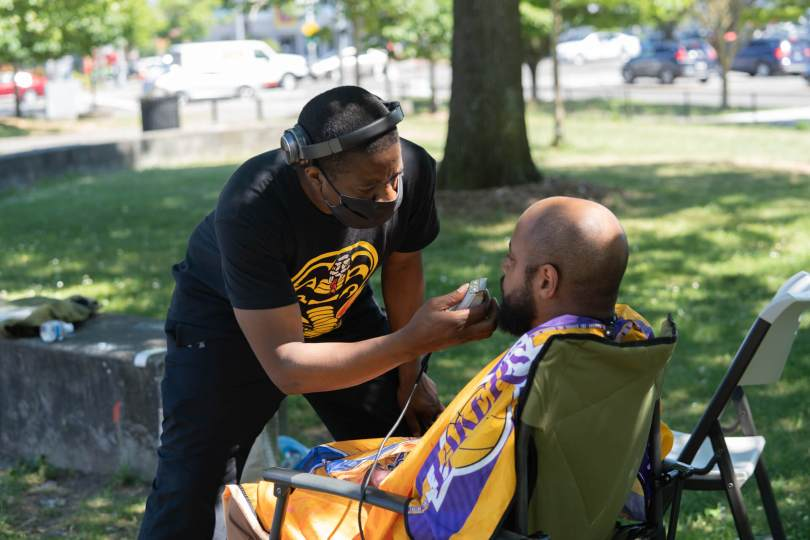 A community barber who donates his services to works with one of his clients.
