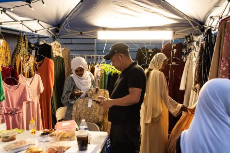 Photo of event attendees shopping inside a vendor's stall full of clothing.