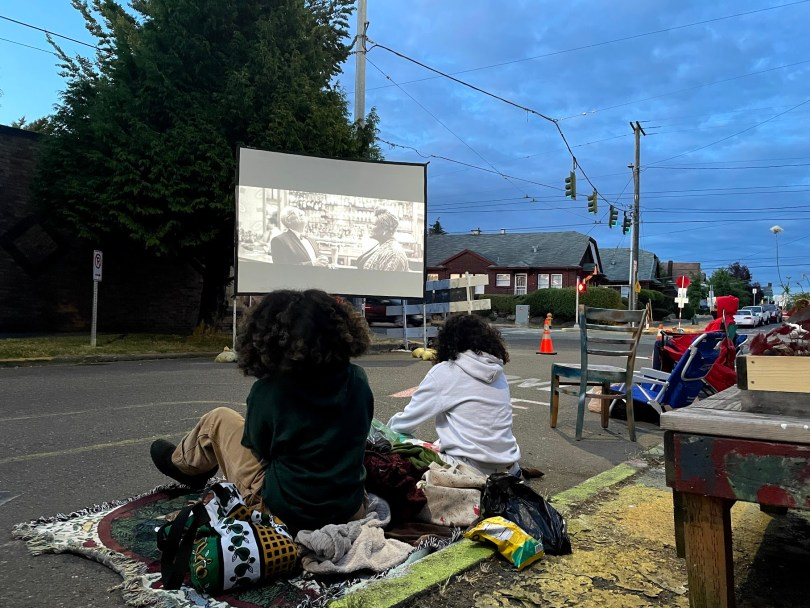 """Movie goers enjoying """"The Forty-Year-Old-Version"""" on the outdoor screen."""