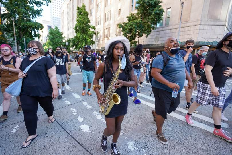 A female-presenting individual plays the saxophone as they march at the #BreatheforKaloni rally.